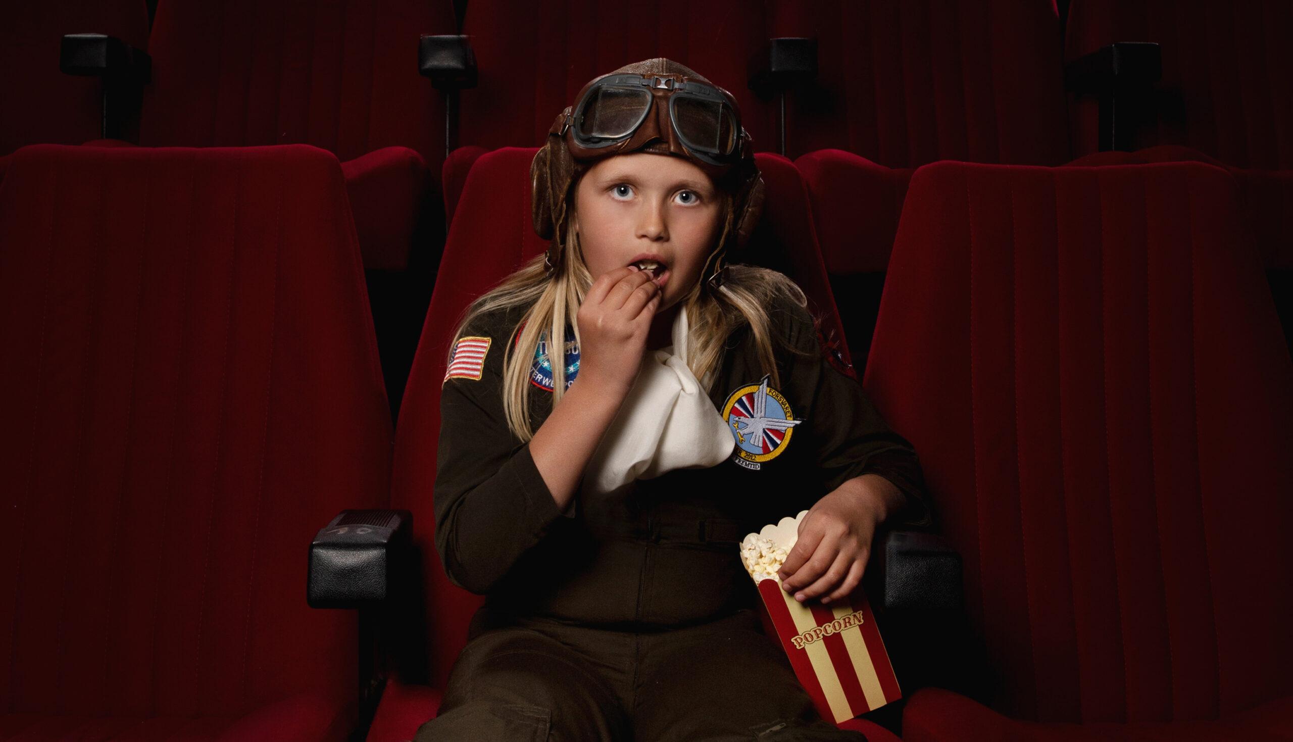 Bilde av jente i pilotdrakt som spiser popcorn i en kinosal