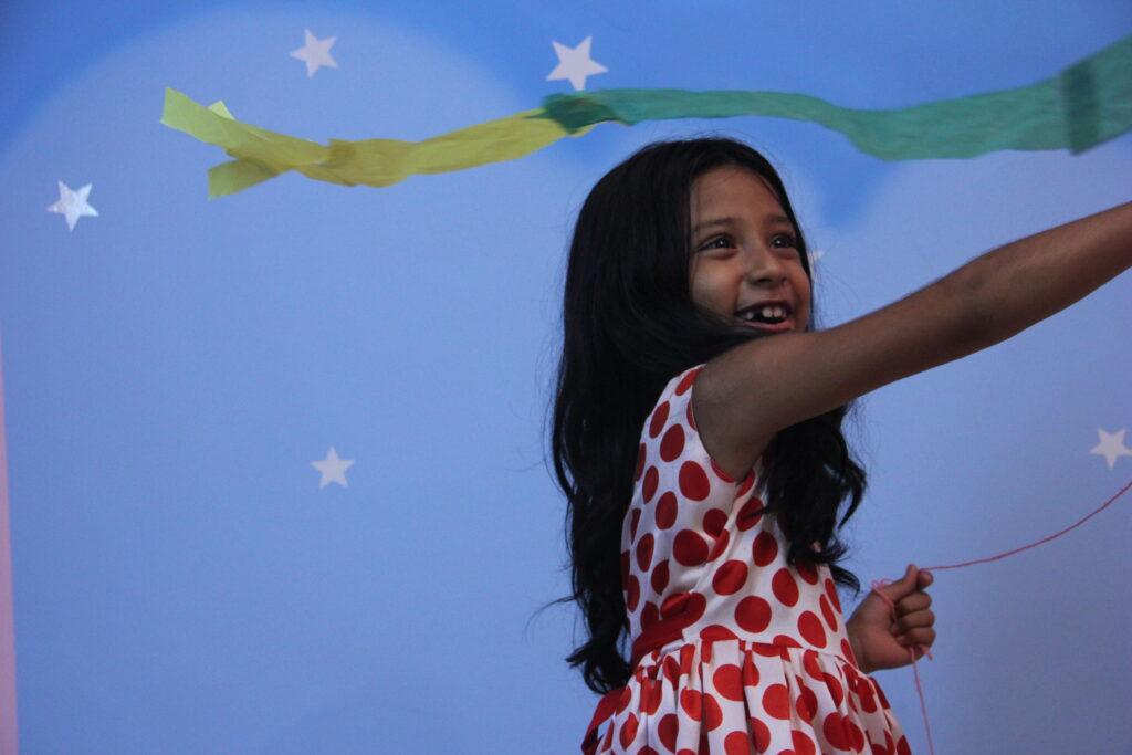 """Stillbilde fra """"How to make a kite"""" av jente som leker med en drage inne."""