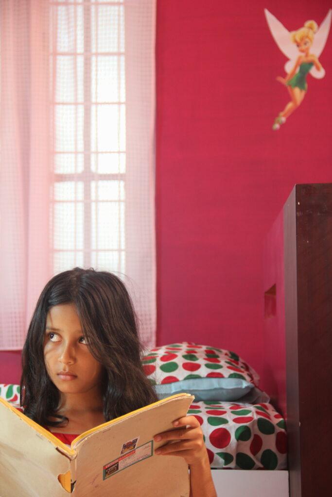 """Stillbilde fra filmen """"How to make a kite"""" av jente som ser ventende ut der hun leser en bok på rommet sitt."""
